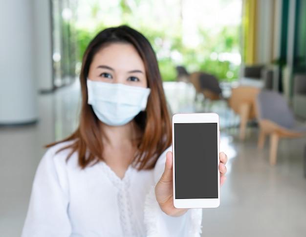 Mooie jonge aziatische vrouw met beschermend gezichtsmasker met smartphone