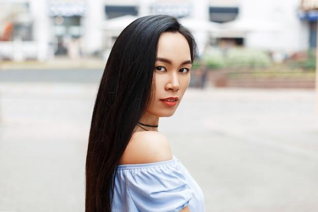 Mooie jonge aziatische vrouw met blote schouders in de stad