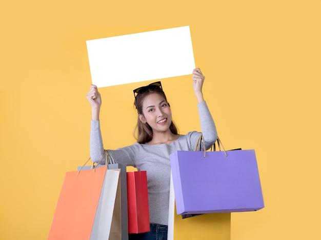 Mooie jonge aziatische vrouw met boodschappentassen en holging witte banner met kopie ruimte geïsoleerd op gele achtergrond