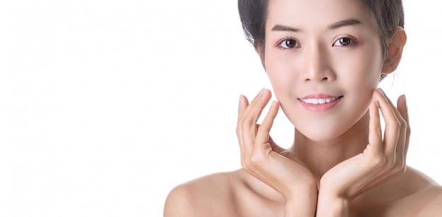 Mooie jonge aziatische vrouw met cosmetica op eigen gezicht