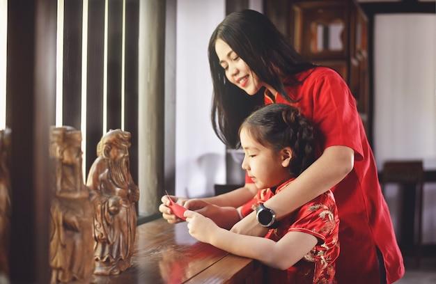Mooie jonge aziatische vrouw met een meisje vieren nieuwe maanjaar in het huis