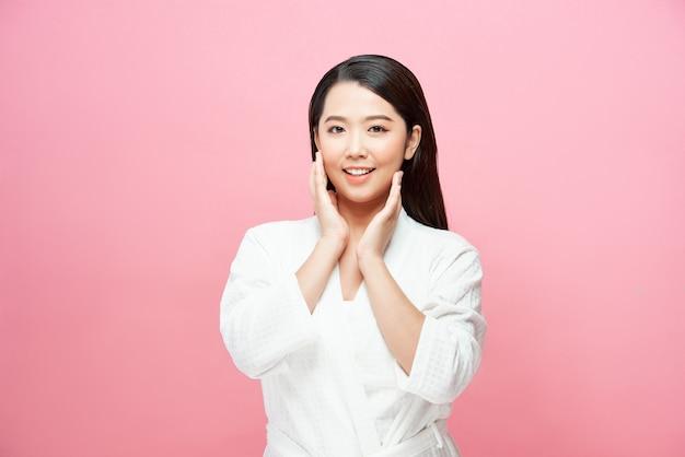 Mooie jonge aziatische vrouw met een schone, frisse huid raakt het eigen gezicht aan, gezichtsbehandeling, cosmetologie, schoonheid en spa,