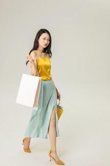 Mooie jonge aziatische vrouw met geïsoleerde boodschappentassen