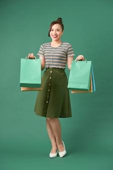 Mooie jonge aziatische vrouw met gekleurde boodschappentassen over groen