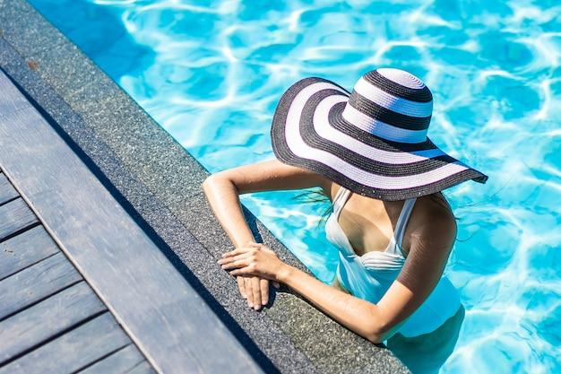 Mooie jonge aziatische vrouw met hoed in zwembad voor reis en vakantie