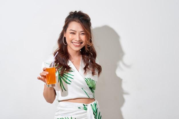 Mooie jonge aziatische vrouw met jus d'orange in tropisch overhemd op witte achtergrond