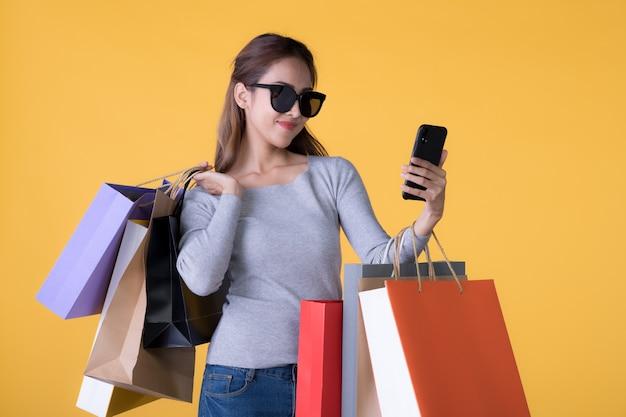 Mooie jonge aziatische vrouw met kleurrijke boodschappentassen en smartphone geïsoleerd op een gele pagina