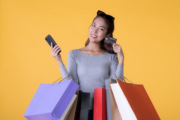 Mooie jonge aziatische vrouw met kleurrijke boodschappentassen met slimme telefoon en creditcard geïsoleerd op gele muur
