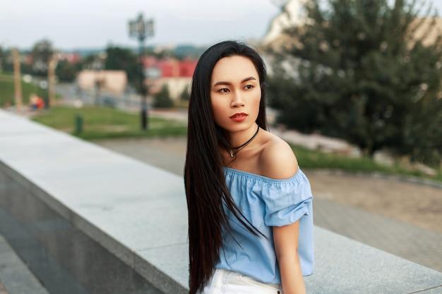Mooie jonge aziatische vrouw met lang haar die in het park rusten