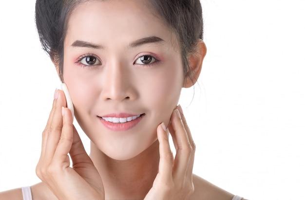 Mooie jonge aziatische vrouw met poeder, spons en cosmetica op eigen gezicht