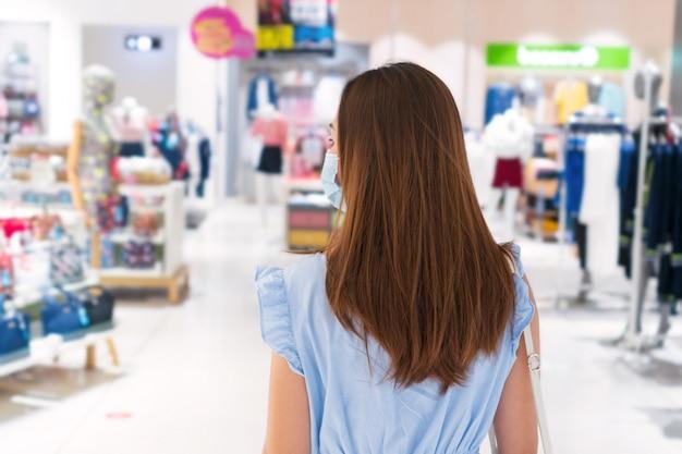 Mooie jonge aziatische vrouw met ptotective gezichtsmasker wandelen in winkelcentrum of warenhuis,