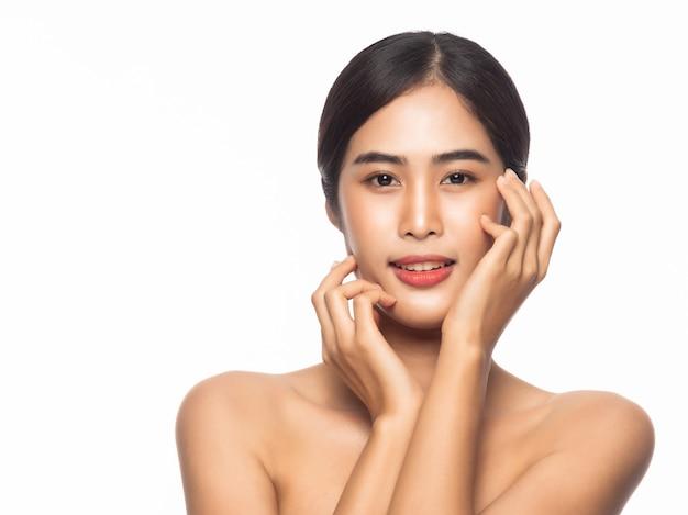Mooie jonge aziatische vrouw met schone huid en handen aanraken gezicht