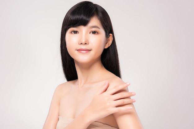 Mooie jonge aziatische vrouw met schone huid. gezichtsverzorging, gezichtsbehandeling, op witte muur, schoonheid en cosmetica concept
