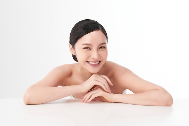 Mooie jonge aziatische vrouw met schone huid op wit