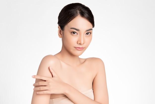 Mooie jonge aziatische vrouw met schone huid op witte muur, gezichtsverzorging, gezichtsbehandeling, cosmetologie, schoonheid en spa, aziatisch vrouwenportret