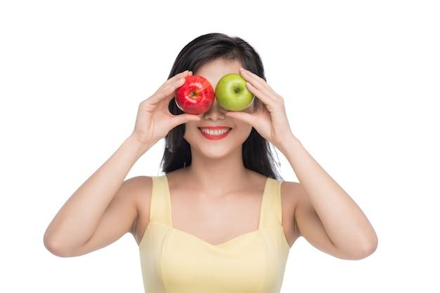 Mooie jonge aziatische vrouw met verse appels geïsoleerd op een witte achtergrond.