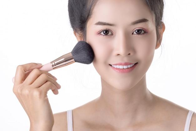 Mooie jonge aziatische vrouw met zachte borstel en cosmetica op eigen gezicht.