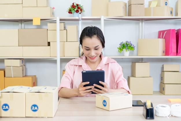 Mooie jonge aziatische vrouw online verkoper verpakken en controleren op inkomende bestellingen in het magazijn