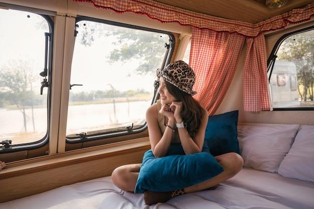 Mooie jonge aziatische vrouw ontspannen en kijken naar het uitzicht in de camper op de camping 's avonds
