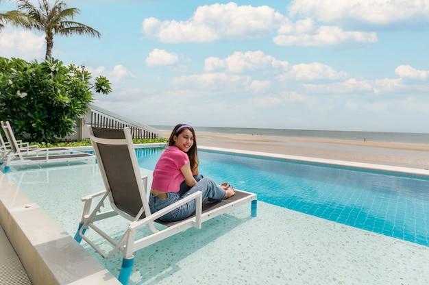 Mooie jonge aziatische vrouw ontspannen en zonnebaden op lounge stoel in zwembad op tropische zee. zomer en vakantie concept