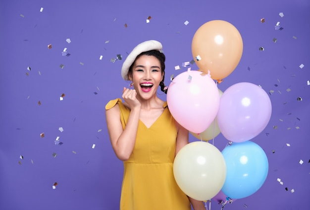 Mooie jonge aziatische vrouw op feest feest met kleurrijke ballon en opgewonden gezicht met confetti die overal op haar valt. gelukkig nieuwjaar of verjaardagsavond vieren concept.