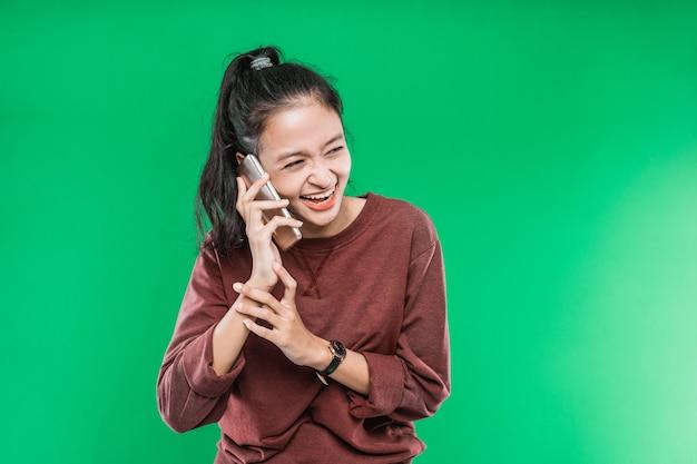 Mooie jonge aziatische vrouw praat aan de telefoon met expressie lach gelukkig geïsoleerd tegen de groene achtergrond