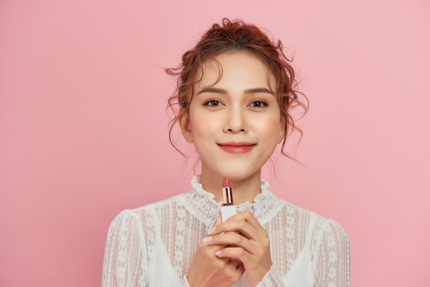 Mooie jonge aziatische vrouw roze lippenbalsem toe te passen