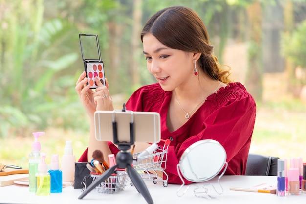 Mooie jonge aziatische vrouw, vlogger, die haar telefoon gebruikt om schoonheidsproducten thuis op een videoblog te tonen en te beoordelen