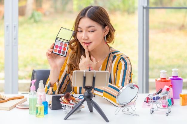 Mooie jonge aziatische vrouw, vlogger, die schoonheidsproducten op een videoblog bekijkt via haar telefoon thuis