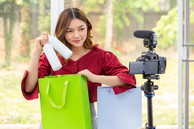 Mooie jonge aziatische vrouw, vlogger, glimlachend naar haar camera terwijl ze de flessen schoonheidsproduct in de tas stopt