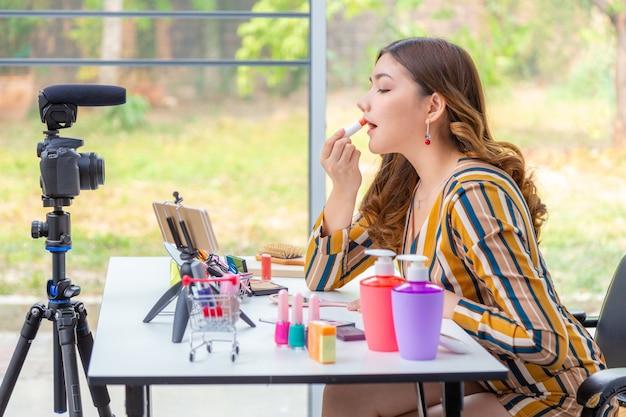 Mooie jonge aziatische vrouw, vlogger, lippenstift make-up op haar lippen zetten tijdens het beoordelen van schoonheidsproducten op een videoblog thuis