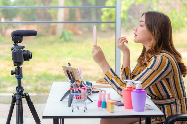 Mooie jonge aziatische vrouw, vlogger, make-up opdoen tijdens het beoordelen van schoonheidsproducten op een videoblog thuis