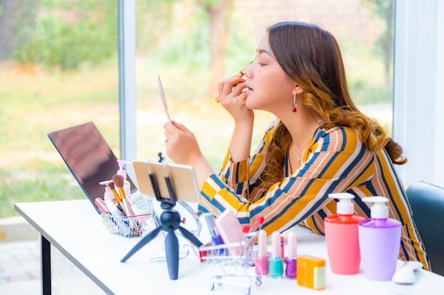 Mooie jonge aziatische vrouw, vlogger, make-up opzetten en schoonheidsproducten bekijken op een videoblog thuis