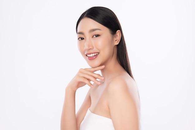 Mooie jonge aziatische vrouw wat betreft haar schoon gezicht met verse gezonde geïsoleerde huid, schoonheidsschoonheidsmiddelen en gezichtsbehandelingsconcept