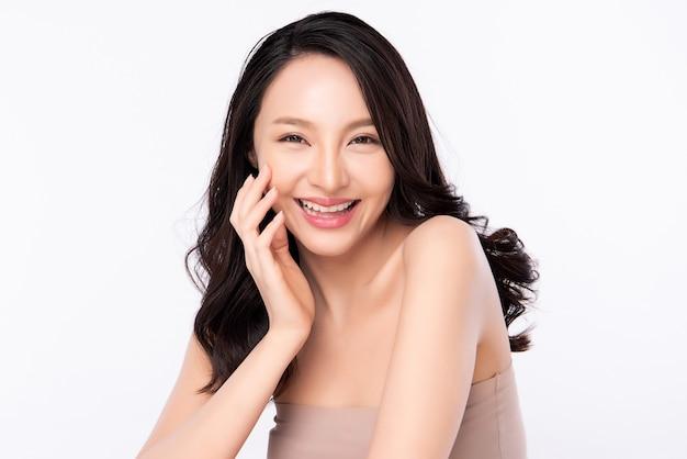 Mooie jonge aziatische vrouw wat betreft haar schoon gezicht met verse gezonde huid, die op witte achtergrond, schoonheidsschoonheidsmiddelen en gezichtsbehandelingsconcept wordt geïsoleerd