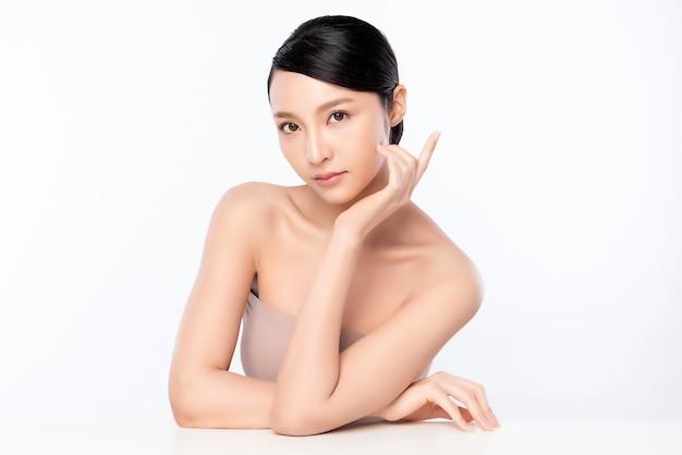 Mooie jonge aziatische vrouw wat betreft haar schoon gezicht met verse gezonde huid, geïsoleerd, schoonheid cosmetica en gezichtsbehandeling concept,