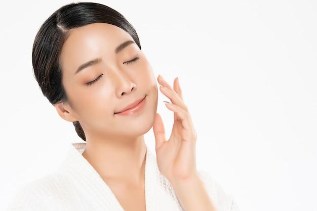 Mooie jonge aziatische vrouw wat betreft zachte wang en glimlach met schone en frisse huid. geluk en vrolijk met ,, beauty and cosmetics concept,
