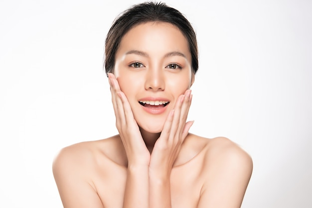 Mooie jonge aziatische vrouw wat betreft zachte wang en glimlach met schone en frisse huid. geluk en vrolijk met, geïsoleerd op wit, schoonheid en cosmetica,