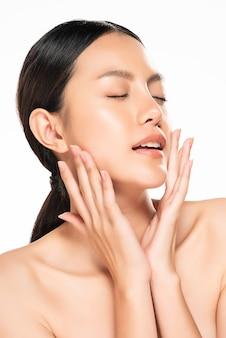 Mooie jonge aziatische vrouw wat betreft zachte wang en glimlach met schone en frisse huid. geluk en vrolijk met, geïsoleerde, schoonheid en cosmetica concept,