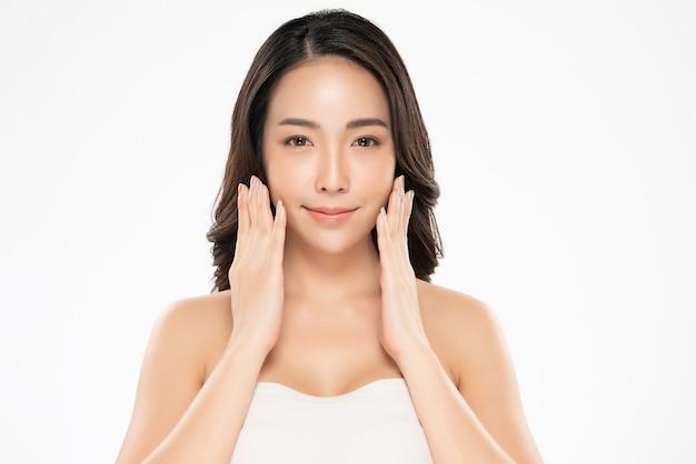 Mooie jonge aziatische vrouw wat betreft zachte wang en glimlach met schone en frisse huid