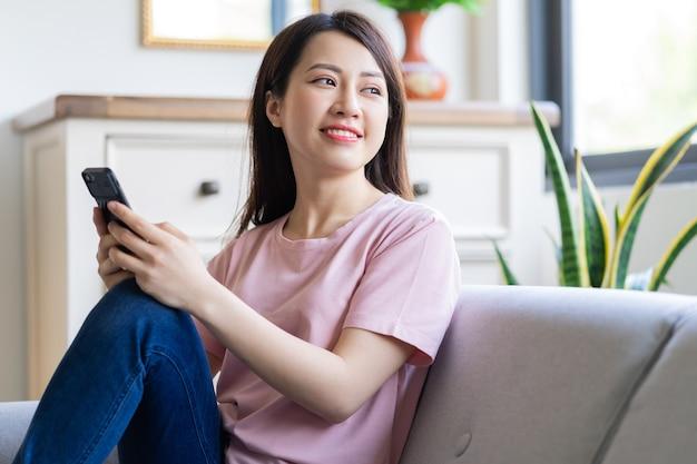 Mooie jonge aziatische vrouw zittend op de bank met behulp van haar telefoon en kijkt uit het raam