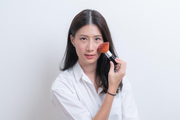Mooie jonge aziatische vrouwelijke model zetten blush met cosmetische borstel in wit overhemd