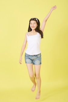 Mooie jonge aziatische vrouwen die met zonnebril op haar hoofd op gele achtergrond springen