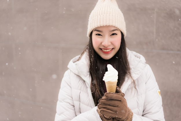 Mooie jonge aziatische vrouwenglimlach en gelukkig met roomijs in sneeuw wintertijd