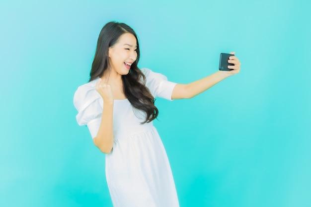Mooie jonge aziatische vrouwenglimlach met smartphone op blauw