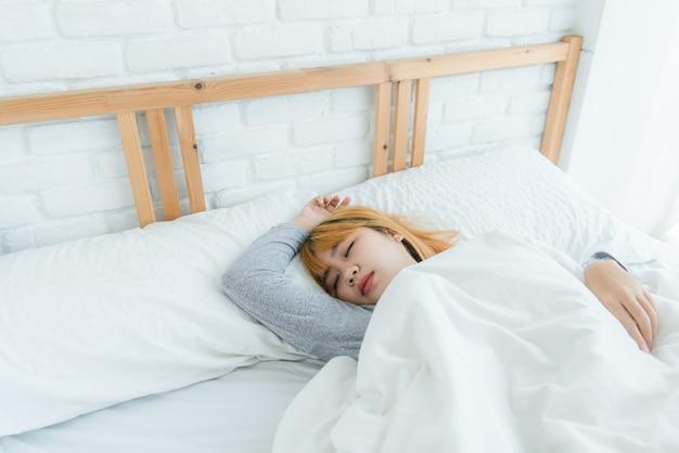 Mooie jonge aziatische vrouwenslaap in bed in de ochtend Gratis Foto
