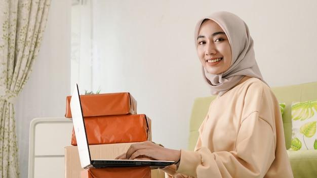 Mooie jonge aziatische zakenman die bestellingen afhandelt met zijn laptop