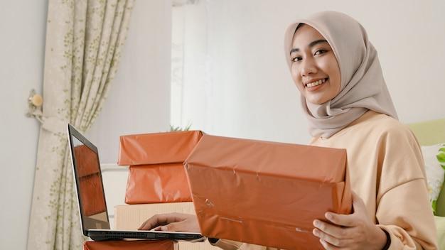 Mooie jonge aziatische zakenman die bestellingen voorbereidt om aan klanten te worden verpakt