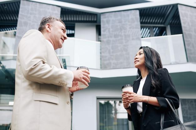 Mooie jonge aziatische zakenvrouw die met een oudere collega praat wanneer ze buiten koffie drinken