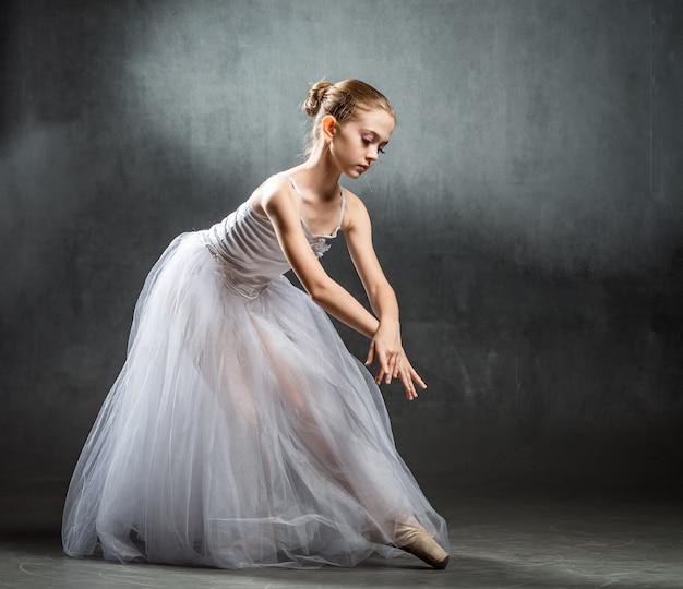 Mooie jonge ballerina danst in de studio op een donkere muureen kleine danser. balletdanser.